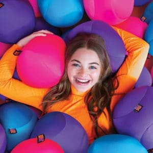 Lifestyle shot of a girl laying in a pile of Nee Doh Dohzee Pillows