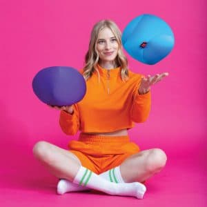 Lifestyle shot of woman juggling purple and blue Dohzee balls while sitting