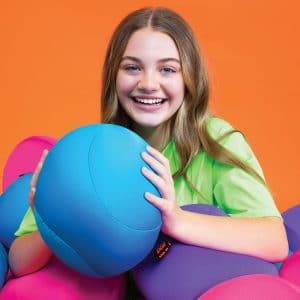 Lifestyle shot of a girl holding a blue Nee Doh Dohzee sitting in a pile of assorted Dohzee balls
