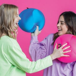 Lifestyle shot of two women playing with a blue and pink Nee Doh Dohzee