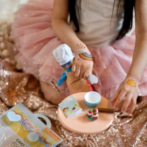 Girl playing with a Lottie doll dressed in the Cake Bake Outfit and accessories on a small play table