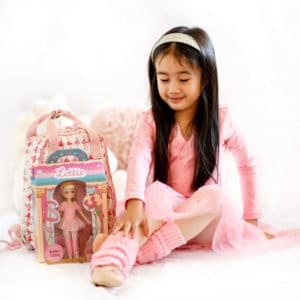 Girl in matching ballet costume sits next to boxed Ballet Class Lottie