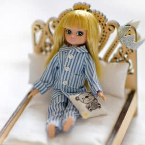 Pajama Party Lifestyle Shot - Lottie doll wearing striped pajamas on a small bed