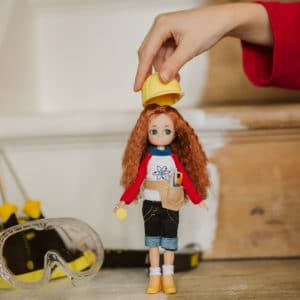 Lifestyle shot of a child placing hard hard on Young Inventor Lottie doll