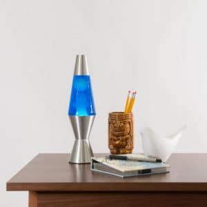 """11.5"""" LAVA® Lamp – White/Blue/Silver on table with notebook and tiki mug"""