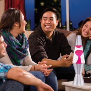 """11.5"""" LAVA® Lamp – Pink/Clear/Silver on a coffee table at a party"""