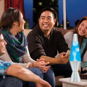 """14.5"""" LAVA® Lamp – White/Blue/Silver on a coffee table at a party"""
