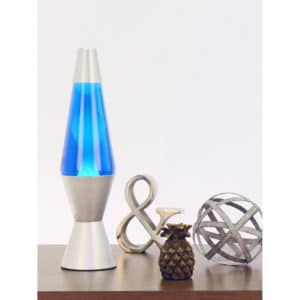 """14.5"""" LAVA® Lamp – White/Blue/Silver on a table with knick knacks and figurines"""