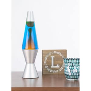 """14.5"""" LAVA® Lamp – Orange/Blue/Silver on shelf with candle and sign"""