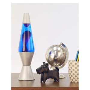 """14.5"""" LAVA® Lamp – Purple/Blue/Silver on table with scotty dog figure, silver globe, and a pencil cup"""