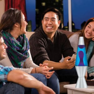 """14.5"""" LAVA® Lamp – Purple/Blue/Silver on a coffee table at a party"""