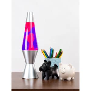 """14.5"""" LAVA® Lamp – Pink/Purple/Silver on table with pencil cup, scotty dog figure, and white piggy bank"""