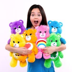 Care Bears medium plush bears being held by girl